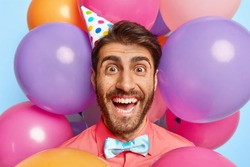 Lucky cheerful man with happy look, makes photo against party attributes, wears cone paper hat, elegant bowtie and rosy shirt, poses with colorful balloons in background. Special occasion concept