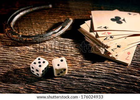 Lucky craps game dice rolling out chance number seven and vintage poker cards with winning aces by old horseshoe for player and gambler good luck charm on rustic wood table in western gambling saloon #176024933