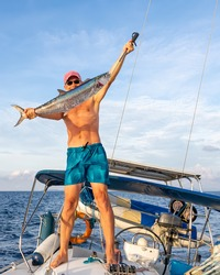 Lucky fisherman on charter sailing yacht with trophy king mackerel (kingfish, wahoo or Scomberomorus cavalla) . Tanned man with sunglasses on sea fishing on a yacht cruise in Indian Ocean.