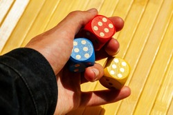 Lucky gambler hand holding three colorful shiny game dice showing number six. Multiple dice show 6, luck in gambling, cheating, dodger, ace up the sleeve, success and lucky numbers abstract concept