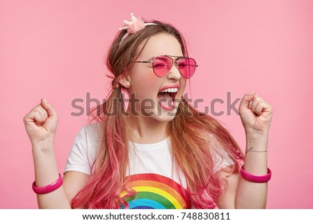 Lucky happy female model rejoices her victory on beauty contest, gets good prize, clenches fists with joy, screams happilly, isolated over pink background. Overjoyed young stylish female winner #748830811