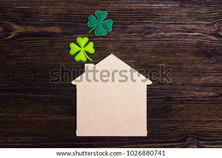 Lucky home symbol with four-leaf clover on wooden background. Copy space. St.Patrick's day holiday symbol.
