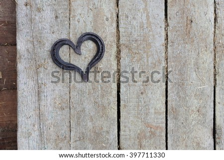 lucky horseshoe, used and with rust, on rustic wooden planks, symbol for good luck, background with copy space #397711330