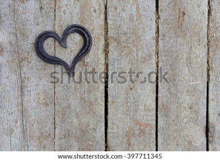 lucky horseshoe, used and with rust, on rustic wooden planks, symbol for good luck, background with copy space #397711345