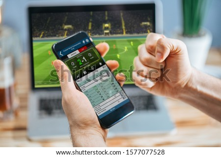 Lucky man celebrating money win. Male fan watching football play online broadcast on his laptop, cheering for his favorite team making bets at bookmaker's website. Foto stock ©