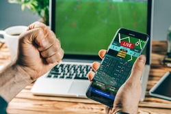 Lucky man celebrating victory after making bets using gambling mobile application on his phone. Football match online broadcast on laptop screen on the background.
