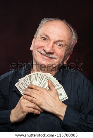Lucky old man holding with pleasure group of dollar bills