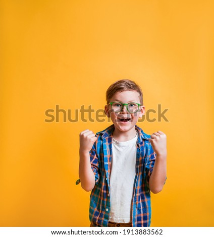 Lucky school boy in glasses isolated on yellow background. Very happy and excited kid boy doing winner gesture with arms raised, smiling and screaming for success. Celebration. Boy superhero