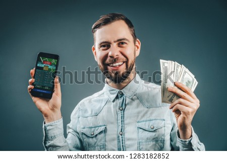 Lucky smiling guy celebrating victory after making bets using gambling mobile application on his phone. Casually dressed bearded business man holding ward of cash in hands.