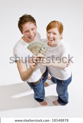 Lucky, wealthy couple excitedly holding group of twenty dollar bills