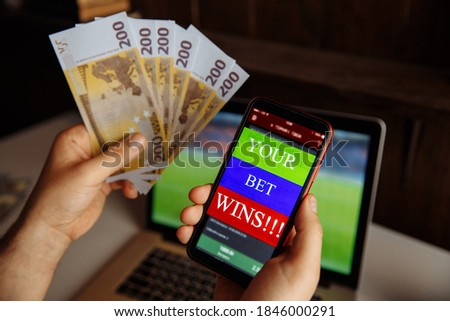 Lucky winner at football betting with euro money in hands near laptop Foto stock ©