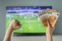 Lucky winner at football betting with euro money in hands near the TV