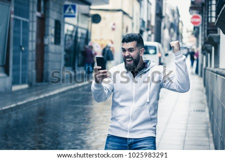 Lucky young man with fist up celebrates victory holding cellphone on rainy street in the city. Full beard hipster model on grey hoodie with euphoric expression. On line bet winner, exultant concept