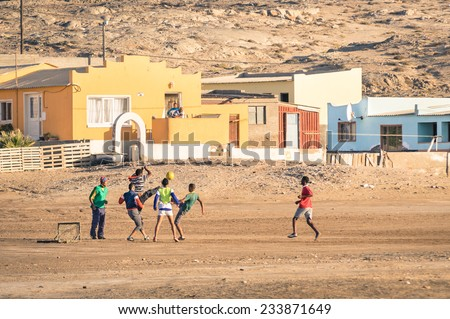 LUDERITZ, NAMIBIA - 24 NOVEMBER 2014: local young people playing football in the playground next to a modern township; for lucky and talented players, soccer is a fast way to escape poverty of slums