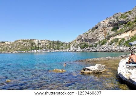 Ludzie pływający i opalając się na kamienistej plaży. Rodos Grecja Zdjęcia stock ©