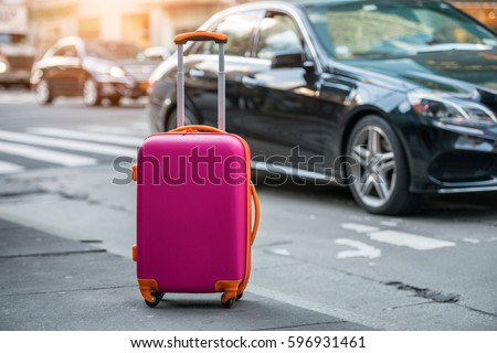 Luggage bag on the city street ready to pick by airport transfer taxi car. stock photo