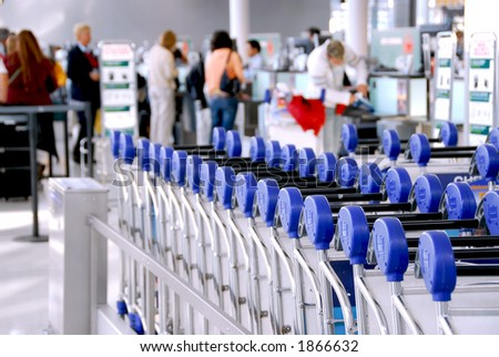 Luggage carts at modern international airport passengers at check-in counter in the background
