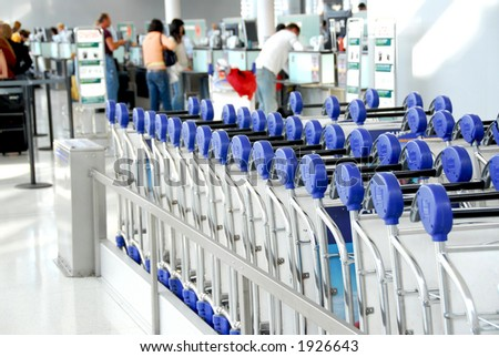 Luggage carts at modern international airport, passengers at check-in counter in the background