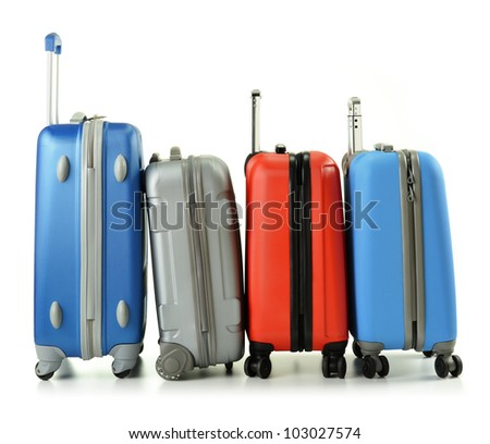 Luggage consisting of four polycarbonate suitcases standing in the row isolated on white