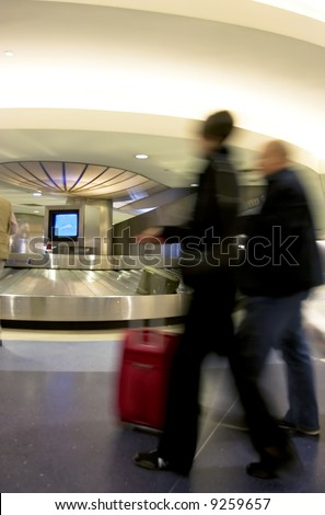 Luggage pick up area in busy airport, with motion-blurred people rushing in the foreground
