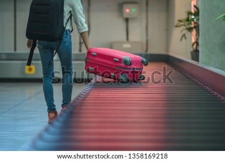 luggage reclaim at the airport in the transfer belt by woman traveler at the last stage of final call, arrival hall of the terminal