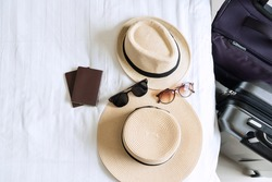 Luggage, straw hat, sunglasses and passport of a couple on bed. Prepare to ravel, relaxation, journey, trip and vacation concepts. Top view and copy space