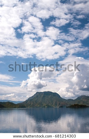 LUGU LAKE, LIJIANG, YUNNAN, CHINA - JULY 2014: Lion Mountain is in the background reflected in Lugu Lake in Lijiang, China. #681214303