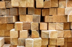Lumber in sawmill, ends of timber blocks for texture background. Sawed and processed wood in warehouse, timber stack in factory yard. Pile of wooden boards in storage. Construction material concept.