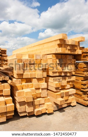 Lumber warehouse in the open air. Wooden beam, planks of wood, stacked in stacks. Sunny day, blue sky with clouds. Vertical photo #1472450477