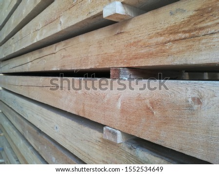 Lumber warehouse in the open air. Wooden beams, planks of wood, stacked in stacks. Horizontal photo