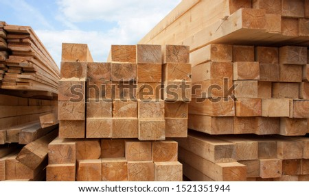 Lumber warehouse. Wood planks and timber stacked in stacks outdoors #1521351944