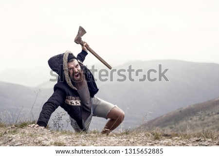 lumberjack. bearded man, long beard, brutal caucasian hipster with moustache holds axe with angry face on mountain top with cloudy sky, unshaven guy with stylish hair getting beards haircut on natural