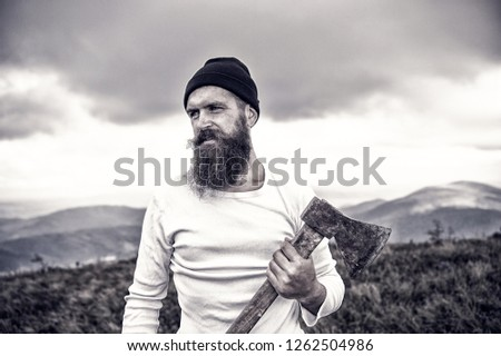 lumberjack. bearded man, long beard, brutal caucasian hipster with moustache holds axe with serious face on mountain top . beard. unshaven guy with stylish hair getting beards haircut