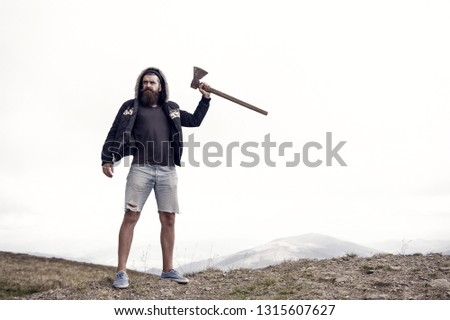 lumberjack. bearded man, long beard, brutal caucasian hipster with moustache holds axe with serious face on mountain top with cloudy sky, unshaven guy with stylish hair getting beards haircut on