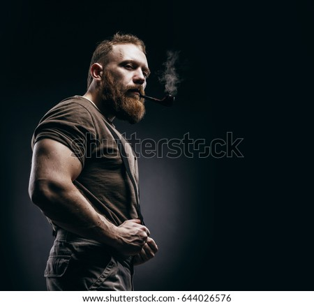 Lumberjack brutal red beard muscled man in brown shirt with smoking tube standing on dark background. Handsome man with red beard and moustache smoking pipe Stock photo ©