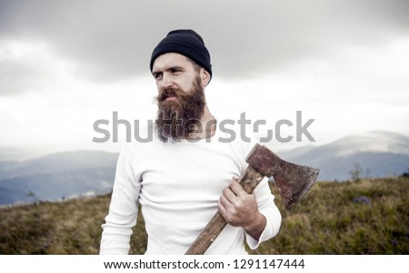 lumberjack. man, long beard, brutal caucasian hipster with moustache holds axe with serious face on mountain top with cloudy sky, unshaven bearded guy with stylish hair getting beards haircut