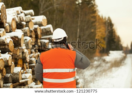 Lumberjack  talking on a mobile phone near log pile