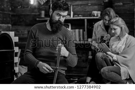 Lumberjack with strict look and long bushy beard whetting razor or knife, danger concept. Bearded man in retro outfit sharpening blade. Girls chatting while reading book in old wooden house. #1277384902