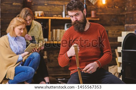 Lumberjack with strict look and long bushy beard whetting razor or knife, danger concept. Bearded man in retro outfit sharpening blade. Girls chatting while reading book in old wooden house. #1455567353
