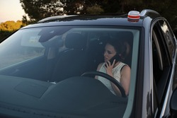 luminous beacon v16. Vehicle damaged with the new emergency light placed on the roof of the vehicle, driver calling for roadside assistance with his mobile phone