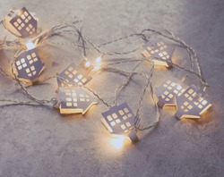 luminous garland with paper houses. New year and Christmas background in light tones.