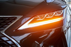 Luminous headlight on a new car in the showroom