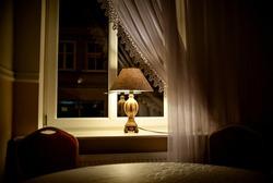 Luminous lamp with a floor lamp on the windowsill