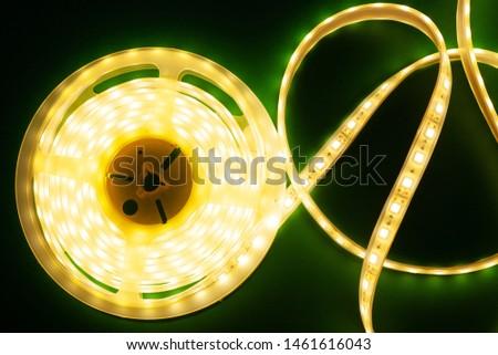 Luminous LED strip on a illuminated dark green background mockup top view, close-up