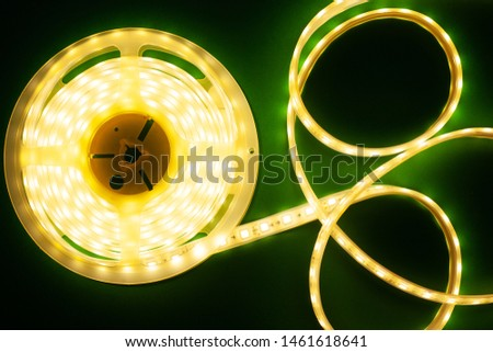 Luminous LED strip on a illuminated dark green background top view, close-up