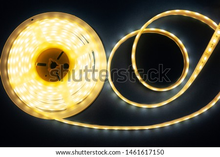 Luminous LED strip on a illuminated silver blue background top view, close-up