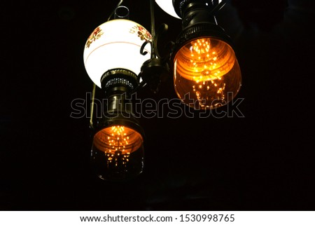 Luminous modern chandelier on the ceiling on a black background isolated #1530998765