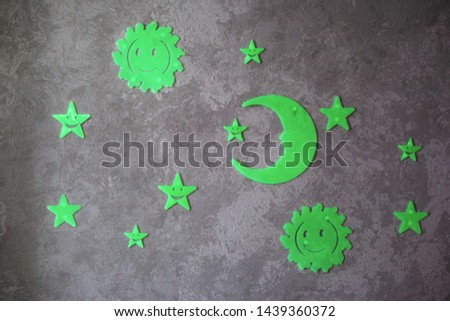 Luminous phosphoric sun, moon and stars on a gray background close-up #1439360372