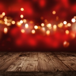 Luminous red christmas background with golden lights in front of an empty wooden table
