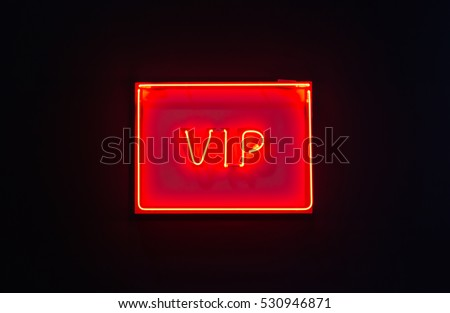 Luminous red neon sign of VIP on a dark background